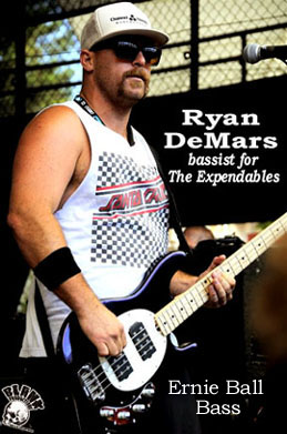 Ryan DeMars bassist for The Expendables palming an Ernie Ball  bass.